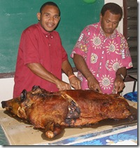 Clovis and Roy carving the roast pig