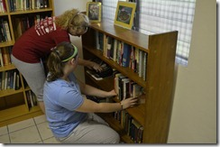 Jenni and Emily arranging the bookshelves