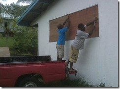 JBI Teachers, Pastors Kiel and Philip nailing plywood over the office windows