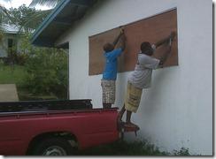 JBI Teachers, Pastors Kiel and Philip nailing plywood over the office windows