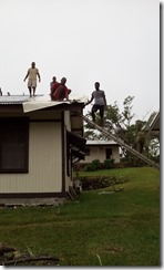 Chapel crew putting canvas over  damaged roof